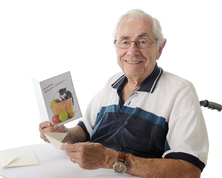 old envelope: Closeup of an elderly man looking up, smiling in his wheelchair, as he holds a greeting card.  On a white background.