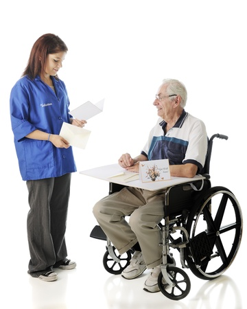 An attractive young volunteer reading a get well card to an elderly man in a wheelchair.  On a white background.