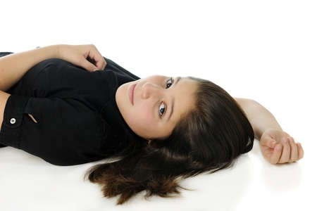 Closeup of an attractive tween girl looking up at the viewer form her reclined position.  On a white background. photo