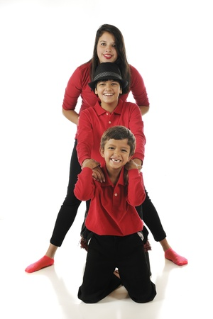 Three mixed race (Asian Indian and caucasian) siblings dressed in red and black, arranged totem-pole style.  On a white background. Stock Photo - 17509993
