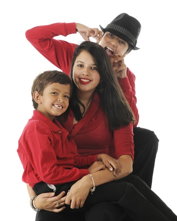 Three biracial siblings (Asian Indian and caucasian) ...a happy preschool boy sitting on the lap of his pretty teen sister with a preteen people-eating monster in a black hat attacking from the rear.  On a white background. photo