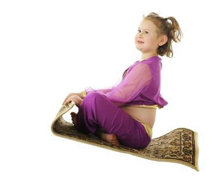A young elementary genie happily riding a flying carpet.  On a white background. Stock Photo