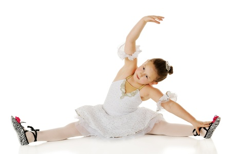 A young ballerina doing stretches in her dancing costume.  On a white background. photo