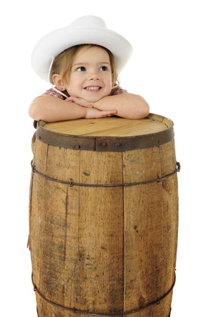 An adorable preschool cowgirl resting her head on a rustic wood barrel.  On a white background with space for your text on the barrel.   photo