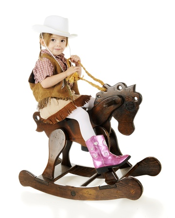 An adorable preschool cowgirl happily riding her wooden rocking horse.  On a white background. photo