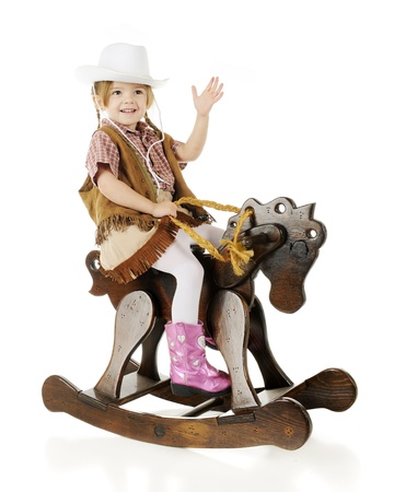 An adorable preschool cowgirl happily waving as she rides her wooden rocking horse.  On a white background. Stock Photo - 17510086