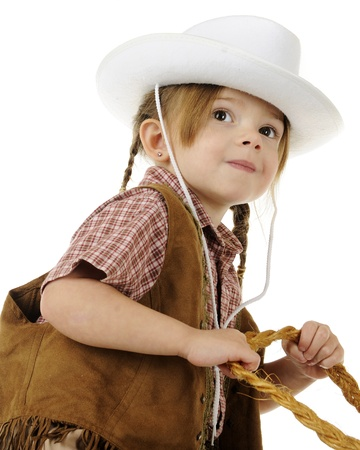 Low angle, closeup image of a preschool cowgirl with her hands on rope reigns.  On a white background. Stock Photo - 17509924