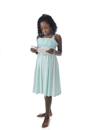 A pretty, barefoot preteen standing in her sundress reading her white Bible.  On a white background. Stock Photo - 17509990