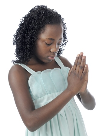Closeup image of a beautiful young tween with her head bowed, eyes closed and hands clasped in prayer.  On a white background. photo