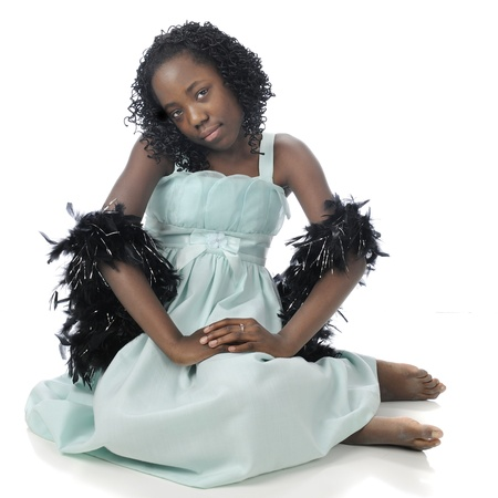 A beautiful tween girl sitting in her soft green dres with black boas draped over her arms.  On a white background. photo