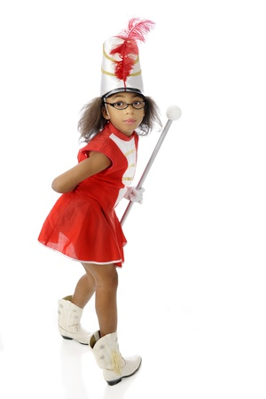 twisting: A young drum majorette twisting around to look at the viewer.  On a white background. Stock Photo