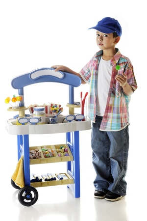 An adorable preschooler looking at the viewer as he stands by his candy stand with his lollipop.  Signs left blank for your text.  On a white background.