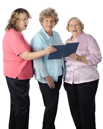 Three senior women singing togethr from a songbook.  On a white background. photo