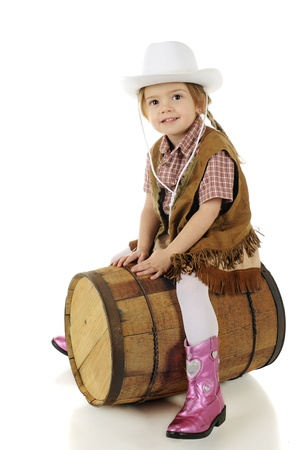 cowgirl boots: A happy preschool cowgirl straddling a rustic wood barrel as if it were a horse   On a white background
