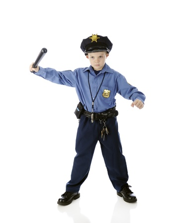A young boy seriously weilding a billy club while wearing his policeman Imagens