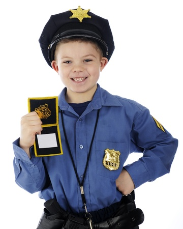 Close-up image of a young elementary  policeman  happily displayng his  official  ID   On a white background