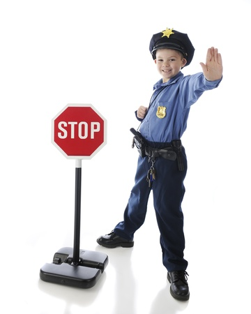An adorable elementary boy gesturing to stop while in his police uniform and standing by a stop sign   On a white background  Imagens