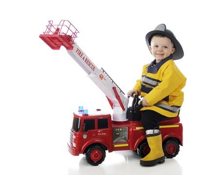 Een schattige peuter gelukkig spelen brandweerman op zijn speelgoed brandweerwagen op een witte achtergrond Stockfoto