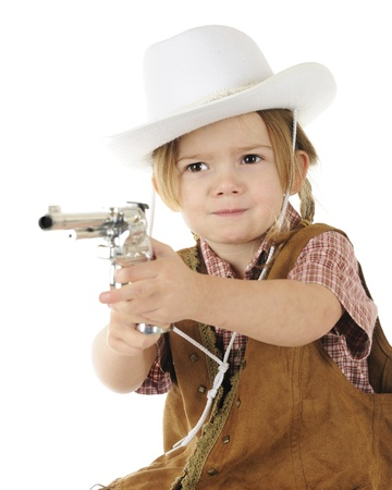 An adorable preschool cowgirl pointing her cap gun with a stern stick em up! attitude.  White background. Stock Photo