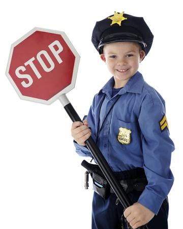 """Een schattige jonge """"politieagent"""" gelukkig met een stopbord. Op een witte achtergrond."""