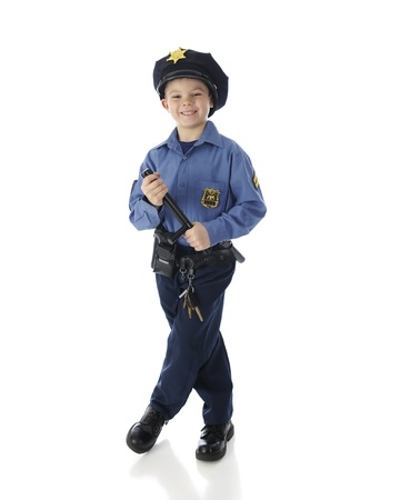 nightstick: An adorable elementary policeman happily standing in his uniform while holding a nightstick.  On a white background. Stock Photo