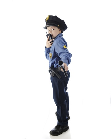 nightstick: Side view of a young elementary boy looking back at the viewer as he holds out his nightstick and talks on his walkie talkie.  On a white background.