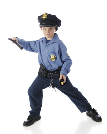 A serious elementary policeman in a protective stance, a flashlight in one hand, his nightstick in the other.  On a white background.