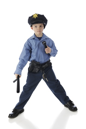 nightstick: Full length portrait of an elementary boy stading alert with his nightstick and flashlight in his police uniform.  On a white background.