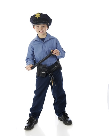 nightstick: Full length image of a young elementary boy happily standing in his police uniform with his nightstick in hand.  On a white background.