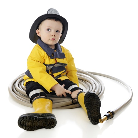 kid sitting: An adorable baby fireman sits in a circle of hose.  On a white background. Stock Photo
