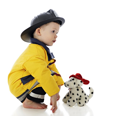 Profile of a baby fireman squatting in front of his toy fire dog.  On a white background. photo