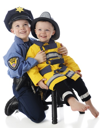Two young brothers posing together -- an elementary boy in a policemans outfit, the toddler dressed as a fire fighter.  On a white background.