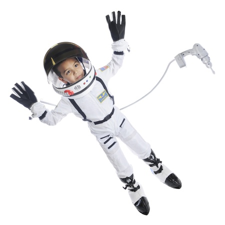 tethered: Full length image of an elementary astronaut in full gear floating in space.  He has an attached dress floating nearby.  On a white background. Stock Photo