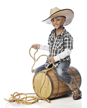 A handsome elementary cowboy happily holding a rope while riding an old barrel.  On a white background.