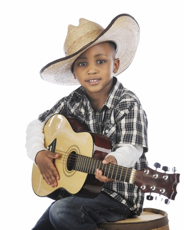 A happy elementary cowboy strumming a guitar while sitting on an old barrel   On a white background  photo