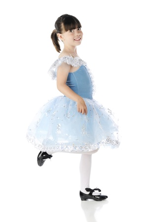 Full length image of a happy elementary girl tap dancing in a beautiful blue and silver dress  On a white background