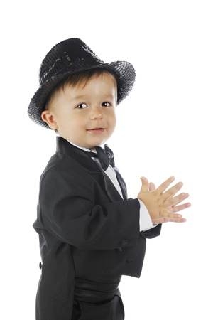 Closeup side view of a toddler in a black tuxedo and a sparkly fedora   On a white background  photo