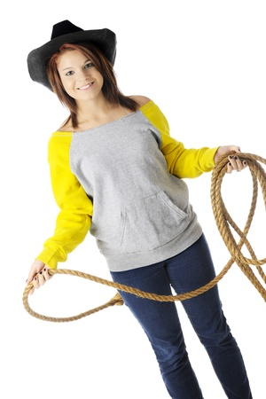 A beautiful teen  cowgirl  in a sloppy, neon yellow and gray sweatshirt   She wears a black hat and is holding a rope   On a white background  photo