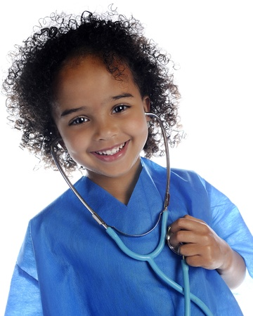 Portrait of an adorable preschool  doctor  in scrubs happily listening to her own heart through a stethoscope   On a white background