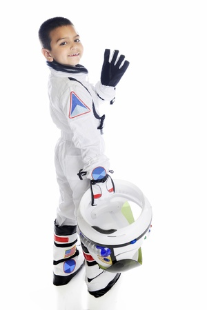 An elementary aged astronaut turning and waving as he walks away from the viewer with his helmet in hand.  On a white background. photo
