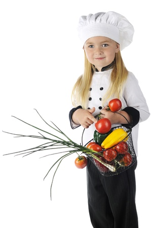 A beautiful preschool chef happily holding a wire basket full of fresh veggies.   On a white background.