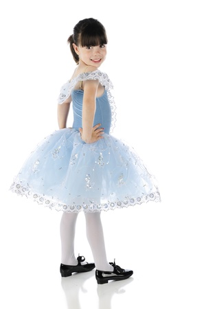 A happy little tap dancer looking back at the viewer in her beautiful blue dance dress.  On a white background. photo