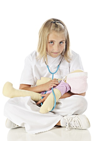lpn: An elementary nurse concentrating as shel listens to her dolls heart.  On a white background.