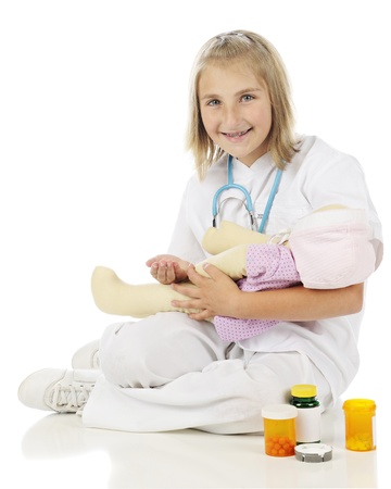 lpn: A happy elementary girl in nursing attire preparing pills for her doll.  On a white background. Stock Photo