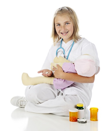 A happy elementary girl playing nurse, preparing medication to give to the doll she holds.  On a white background. photo