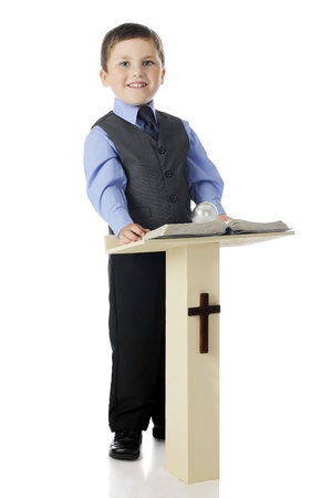 A dressed up elementary boy smiling from his post behind a Christian pulpit holding an opened Bible.  On a white background. Stock Photo