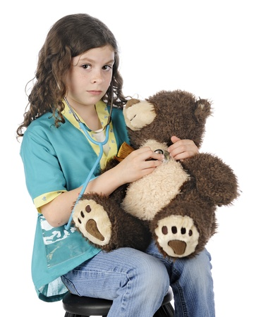 A beautiful elementary vetinarian with a stethoscope listening hard to her toy bears heart.  On a white background. photo