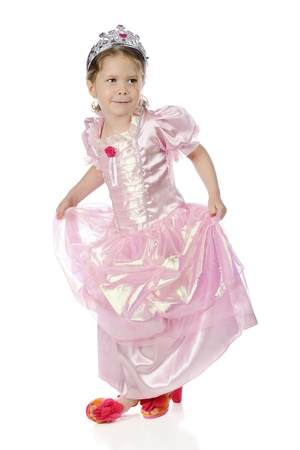 curtsy: A beautiful preschool princess happily taking a bow in her pink princess dress, silver crown and bright pink heels.  On a white background.