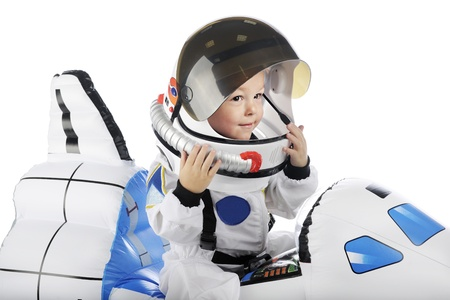 Closeup of an adorable toddler sitting in a shuttle looking out of his astronaut helmet.  On a white background.