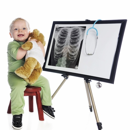 A happy baby hugging his bear while sitting in green scrubs by an eastle displaying a human check x-ray and stethoscope   On a white background  photo